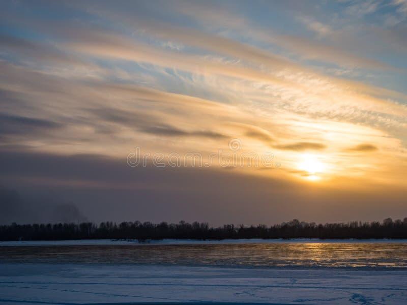 Vintersolnedgång över Obet River med moln, Novosibirsk, Ryssland arkivbild