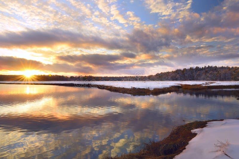 Vintersolnedgång på den härliga reflexionen för flod och för skog av rosa moln i vattnet royaltyfri bild
