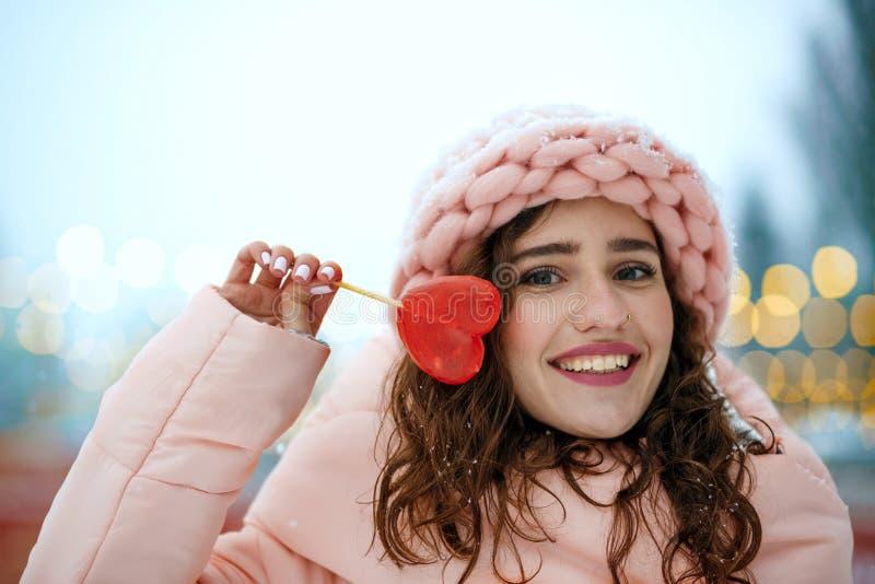 Vinterstående av den flotta unga kvinnan som bär den varma moderiktiga dräkten som rymmer den söta godisen i en hjärtaform Utrymm royaltyfria bilder