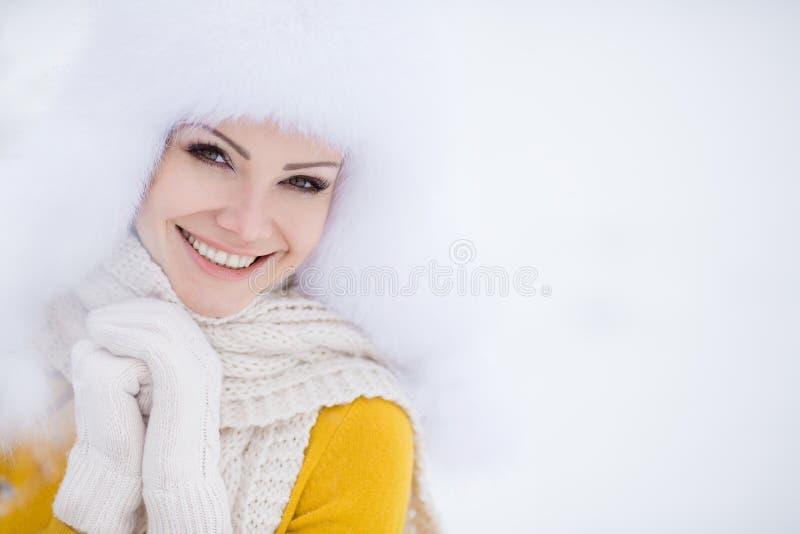 Vinterstående av den härliga le kvinnan med snöflingor i vita pälsar royaltyfri fotografi