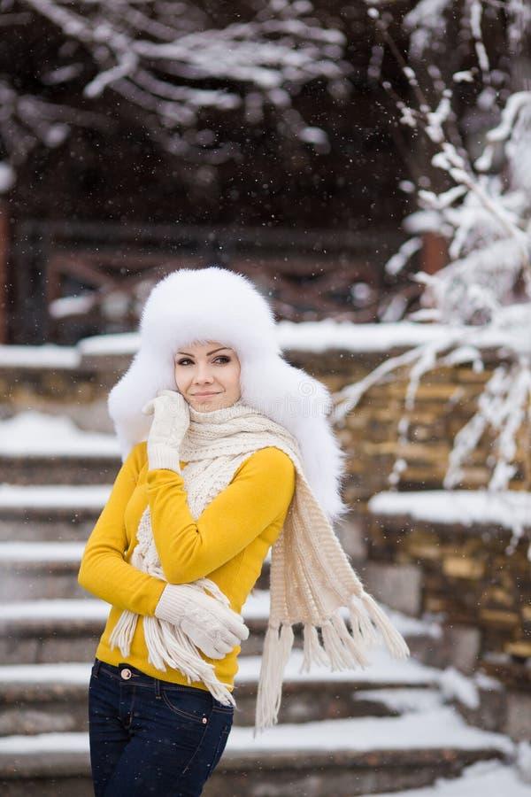 Vinterstående av den härliga le kvinnan med snöflingor i vita pälsar royaltyfria foton