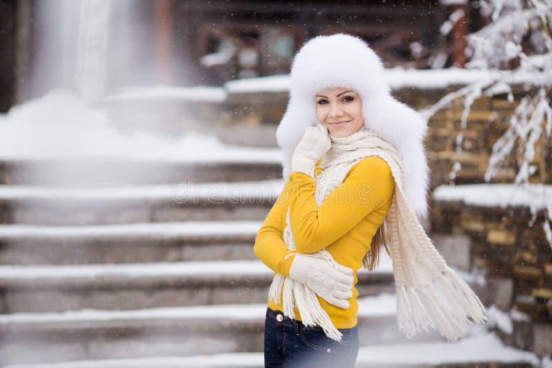 Vinterstående av den härliga le kvinnan med snöflingor i vita pälsar arkivbild