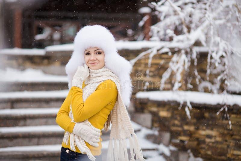 Vinterstående av den härliga le kvinnan med snöflingor i vita pälsar royaltyfri bild