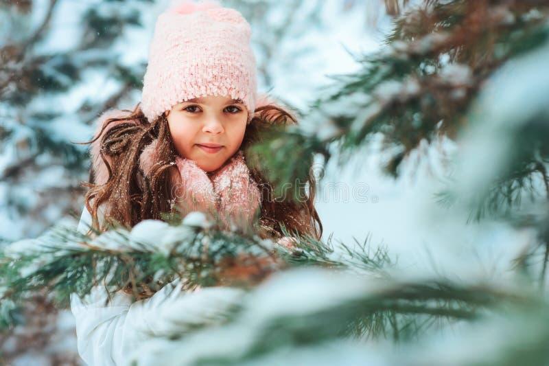 Vinterstående av den lyckliga ungeflickan i det vita laget och hatten och rosa spela för tumvanten som är utomhus- fotografering för bildbyråer