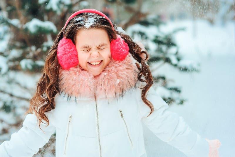 Vinterstående av den lyckliga ungeflickan i det vita laget och hatten och rosa spela för tumvanten som är utomhus- arkivfoton