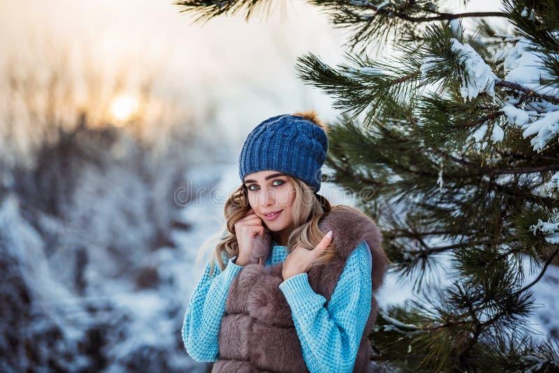 Vinterstående av den unga härliga kvinnan som bär varm kläder Snöa begrepp för vinterskönhetmode arkivbild
