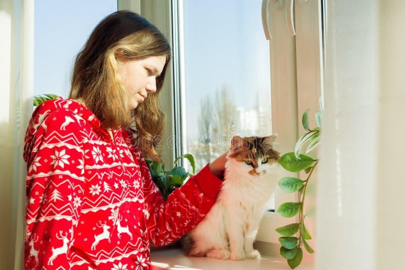 Vintertid hemma, ung flicka i varm pyjamas för vinter med en katt som ut ser fönstret arkivfoto