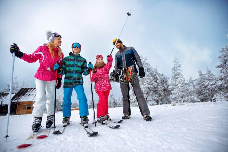 Vintertid och skidåkning - familjen med skidar, och snowboarden skidar på ho arkivbilder