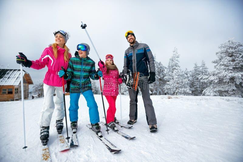 Vintertid och skidåkning - familjen med skidar, och snowboarden skidar på mummel arkivfoto