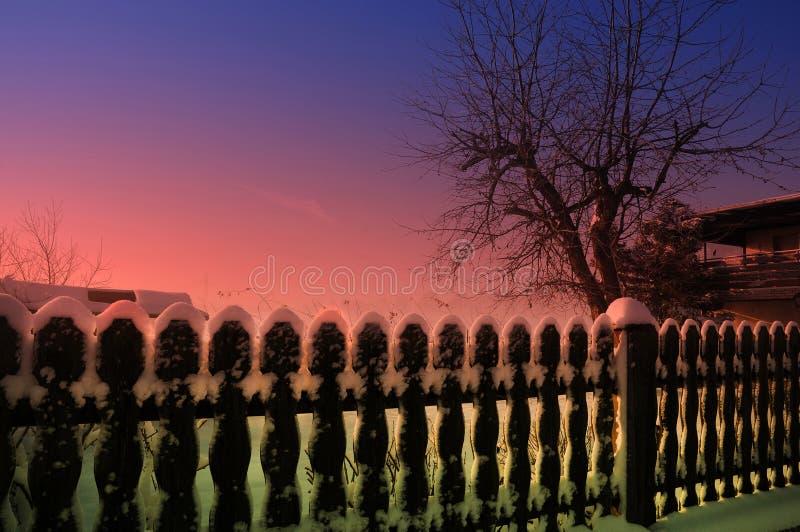 Vintertid, trädgård och staket av min granne som täckas med s royaltyfria bilder