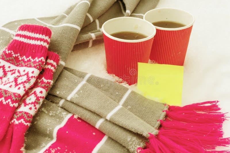 Vintertid, varm klädhalsduk och tumvanten i snön, med två koppar kaffe Gul ren klistermärke för text arkivbild