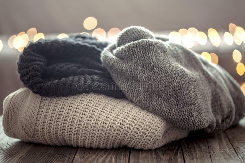 Vintertröjor över bokeh för julljus i hem på trätabellen Semestra garnering, magisk jul arkivbild