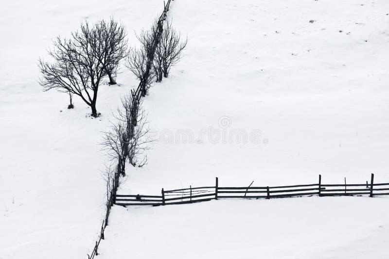 Vintertystnad med trees och trästaket royaltyfria bilder