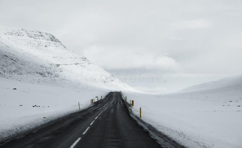 Vinterväglandskap i Island Asfaltväg med från sidan mycket av snö royaltyfri bild