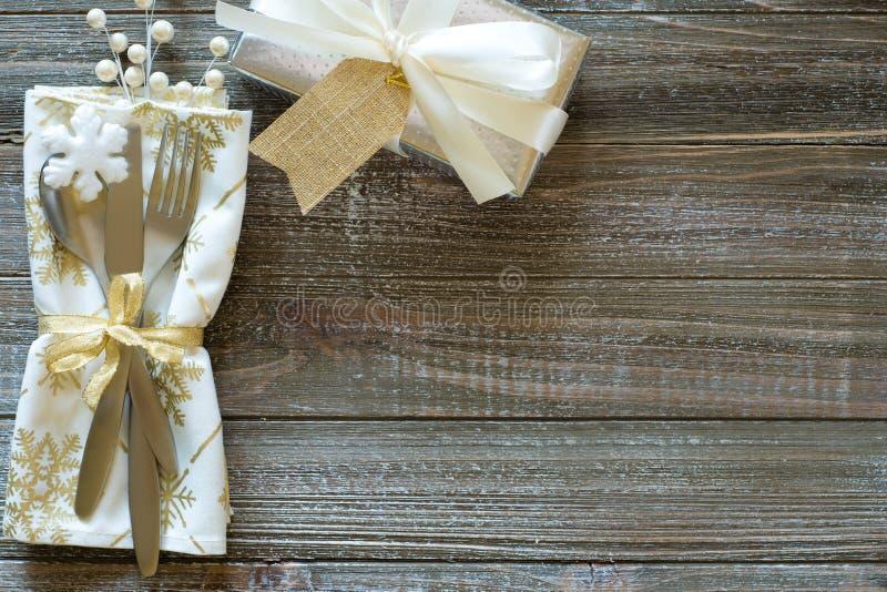 Vintrig inställning för jultabellställe med snöflingaservetten, silvergåva med den vita pilbågen och bär, alla på lantliga träbrä arkivfoton