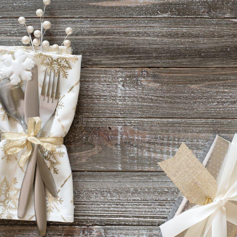 Vintrig inställning för jultabellställe med snöflingaservetten, silvergåva med den vita pilbågen och bär, alla på lantliga träbrä royaltyfri bild