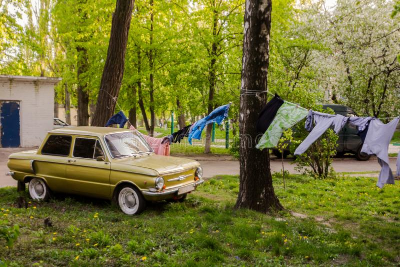 Vintsge sowiecki samochód parkujący w podwórzu budynek mieszkalny Na arkanie na ulicie jest wiszący ubierający odziewa zdjęcie stock