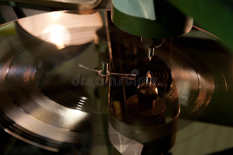 Vinyl disc production. Recording tracks to the vinyl disc form stock images