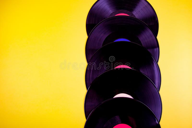 Vinyl discs on background. Five vinyl discks placed  in a vertical line on yellow background stock photography