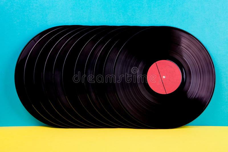 Vinyl discs on background. Many black colored vinyl discks placed  in a  line on yellow and blue background royalty free stock photo