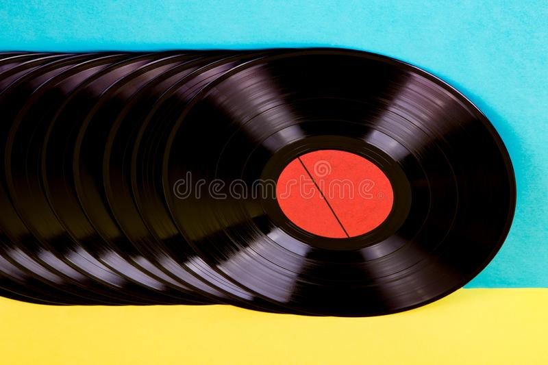 Vinyl discs on background. Many black colored vinyl discks placed  in a  line on yellow and blue background royalty free stock image