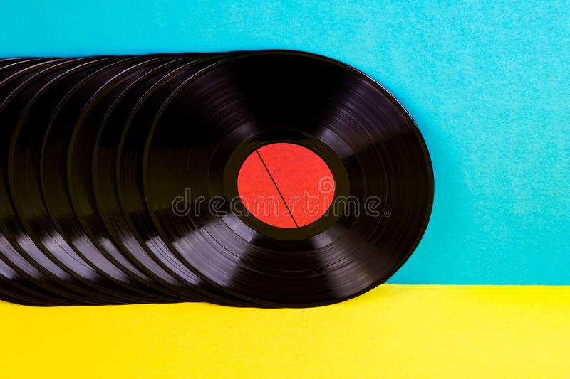 Vinyl discs on background. Many black colored vinyl discks placed  in a  line on yellow and blue background stock image