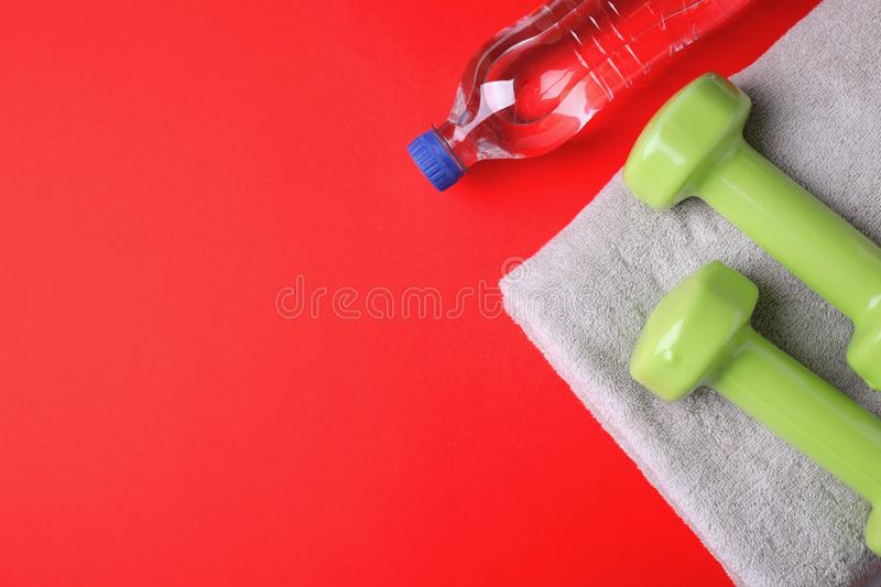 Vinyl dumbbells, towel and bottle of water on color background, flat lay stock photography