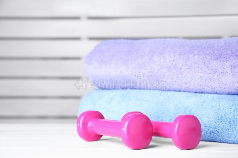 Vinyl dumbbells and towels on table. Space for text royalty free stock images