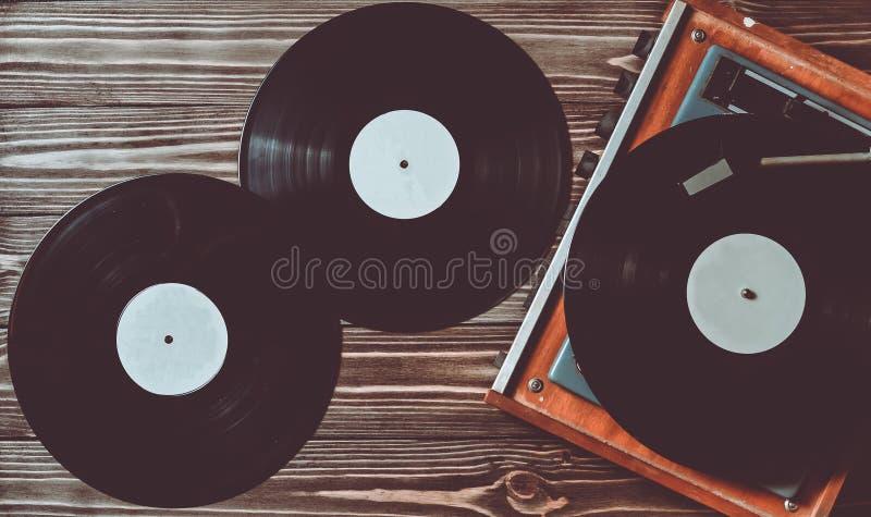 Vinyl player and discs. Gramophone and vinyl discs on a wooden floor. Retro media stock photos