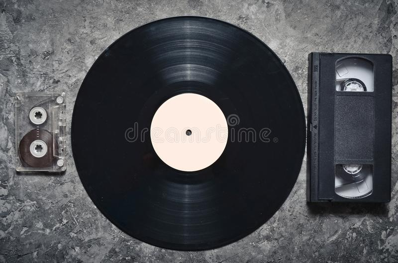 Vinyl record, audio and video cassettes on a gray concrete surface. Retro media technology from the 80s. Top view. stock photos