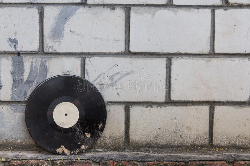 Vinyl record on a background of a retro brick wall. Vinyl record on a background of a brick wall stock images