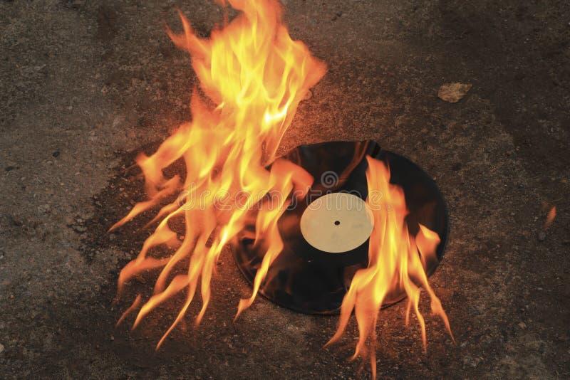 Vinyl record burns bright orange flame on the asphalt. Black musical vinyl plastic in retro style burns on the asphalt with a bright flame royalty free stock photo