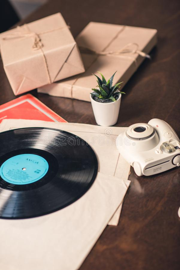 Vinyl record and camera. Vinyl record and instant camera near succulent plant on wooden table stock photos