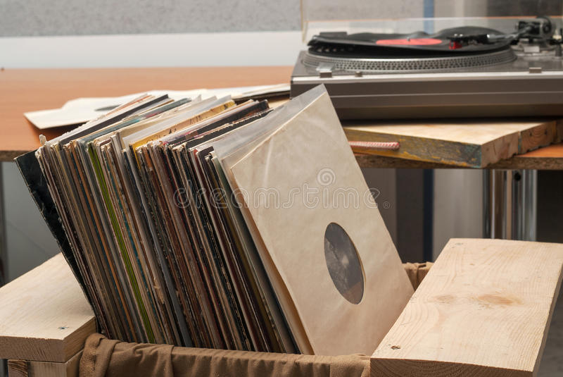 Vinyl record with copy space in front of a collection albums dummy titles, vintage process royalty free stock image