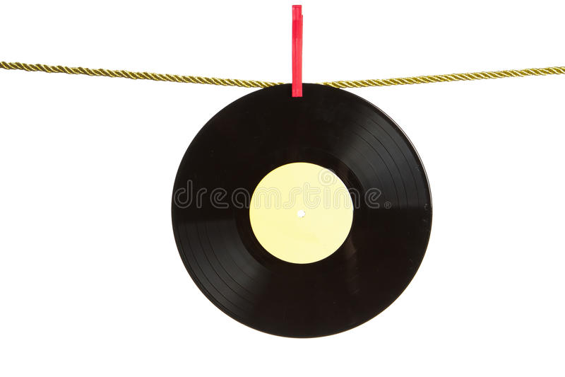 Vinyl record on gold rope. Vinyl record hanged by clothes pin on gold rope isolated over white background royalty free stock photo