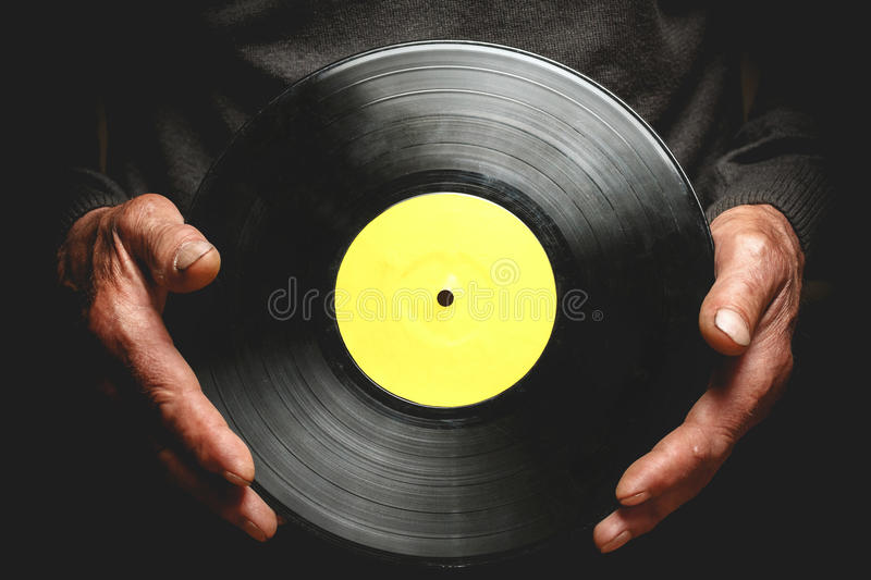 Vinyl record in the hands of old men. Vintage vinyl record in the hands of an elderly man royalty free stock photos