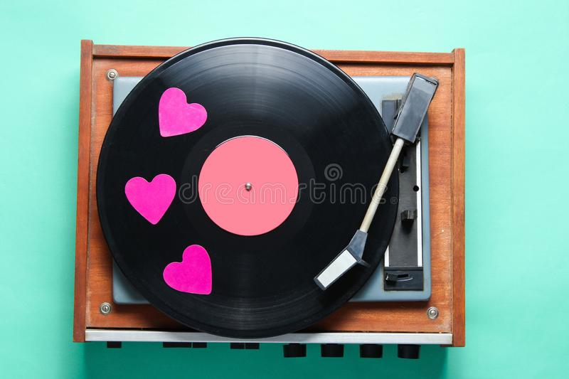 Vinyl record plate. Retro culture, Valentine's Day. Decorative hearts on a vinyl record plate on mint-colored background. Top view, minimalism royalty free stock photo