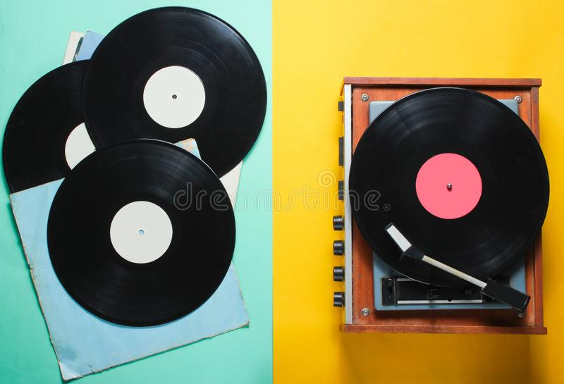 Vinyl record player. Retro style vinyl record player and vinyl records with covers on a colored paper background. Pop culture, Top view royalty free stock photo