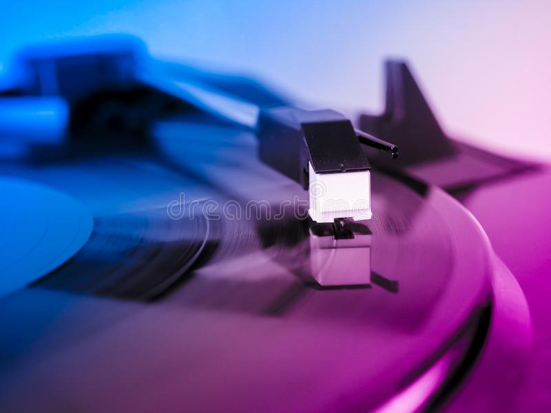 Vinyl record spinning. On a turntable, focus on needle - pink and blue light royalty free stock image