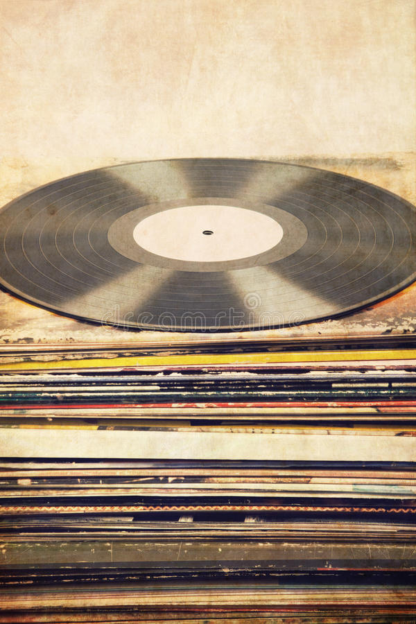 Vinyl record on tower of album covers, textured background, retro look stock image