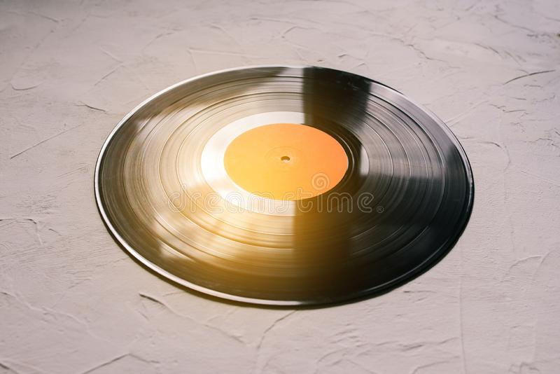Vinyl record on a white background and sun rays. Analog sound. The concept of music, parties. Music background. Vinyl record on a white background and sun rays royalty free stock images