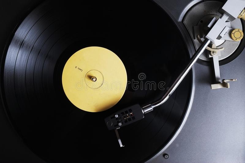 Vinyl record with yellow label playing on a turntable. Overview shot stock images