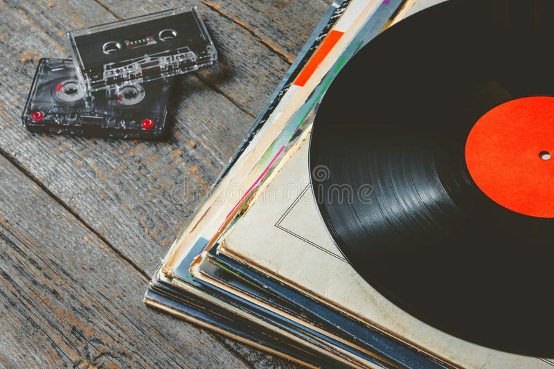 Vinyl records and cassettes. A stack of old vinyl records and cassette tapes are on the board stock photography