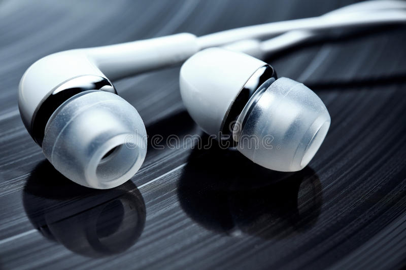 Vinyl records and earphones. Vinyl longplay and white earphones. Classical music records and new technology as a concept of re-mastering royalty free stock photo