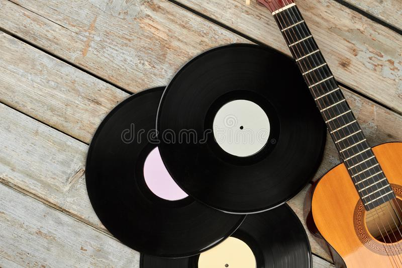 Vinyl records and guitar on wooden boards. stock photo