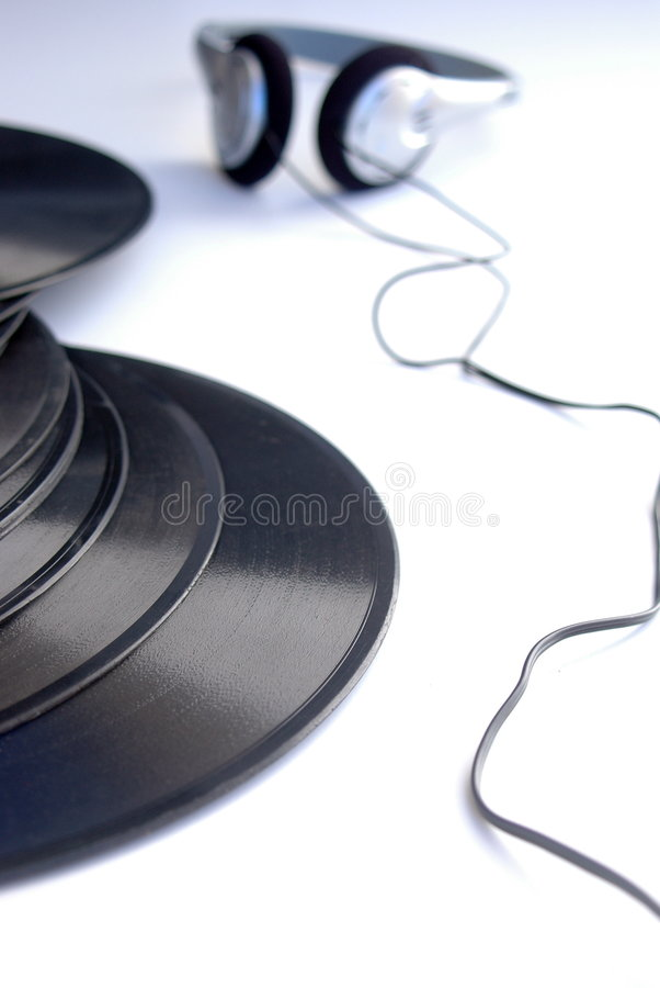 Vinyl records and headphones. Vintage vinyl records and headphones, white background and blue shadows royalty free stock images