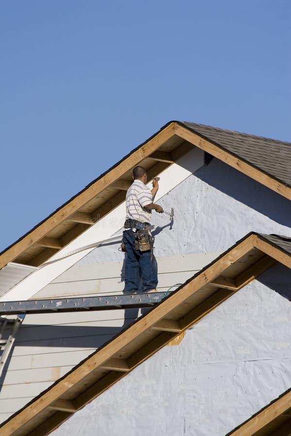 Vinyl siding installation 1. Vinyl siding being installed on a new home under construction stock image