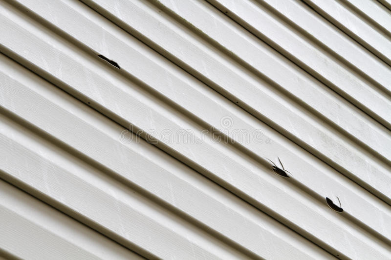 Vinyl Siding Panel Damaged By Hail Storm. Angled shot of a vinyl siding panel on a house damaged by a summer hail storm. The hail that did this damage was golf stock images