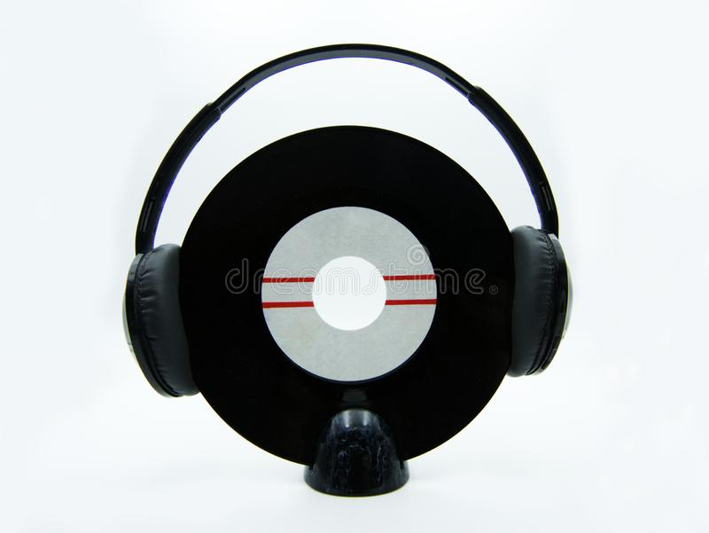 Vinyl single record with black headphones on white background royalty free stock image