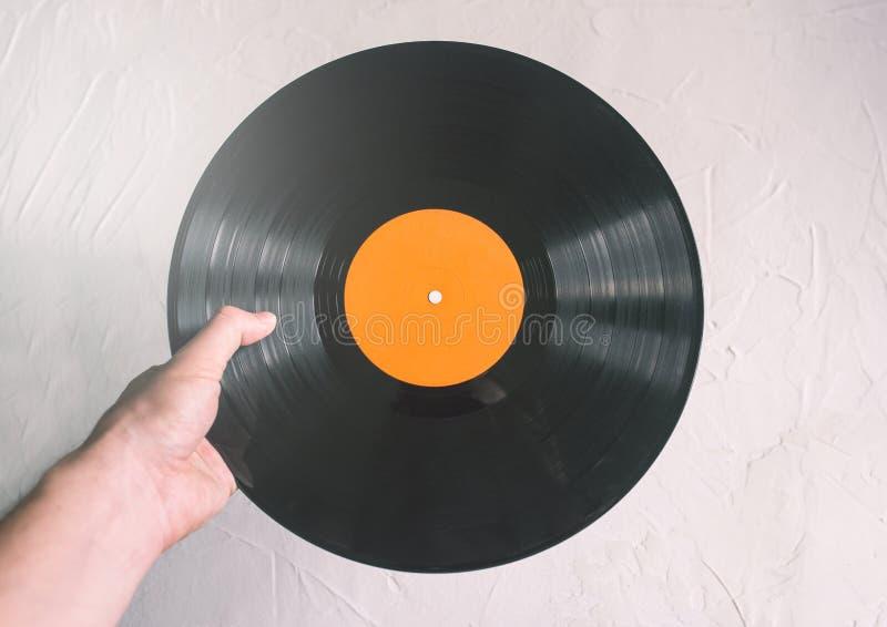 Vinylaufzeichnung in einer männlichen Hand Ein Mann beschließt Musik, um auf einem Vinylspieler zu hören Partei- oder Discokonzep lizenzfreie stockfotografie